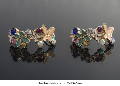 gold earrings with flower isolated on black