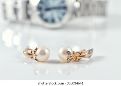 Gold earrings with pearl on the background of women's watches