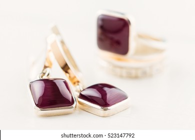 Gold earrings square shaped with purple gemstones on white