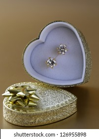 gold earrings stud with diamonds in a gold box