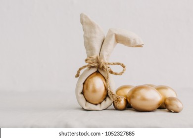 Gold Easter Eggs in Natural Linen Textile. Eco Hipster Concept