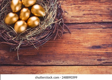 Gold eggs in nest from hay on wood boards with copyspace