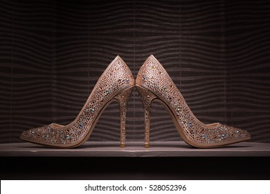 Gold elegant jewel encrusted wedding shoes against contemporary wallpaper background