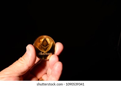 Gold Ethereum ether coin being held up on the left lower corner of the image leaving plenty or room for text.