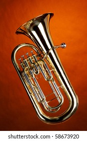 A gold Euphonium tuba baritone horn isolated against an orange background in the vertical format.