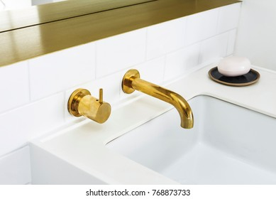 gold faucet and white ceramic sink