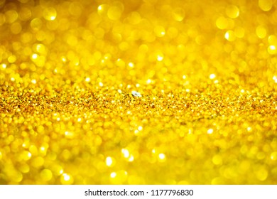 Gold Festive Christmas background. Abstract blurred twinkled bright background with Sprinkle gold dust in the dark with copy space.