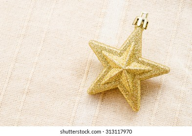 Gold five pointed star christmas decoration on fabric background.