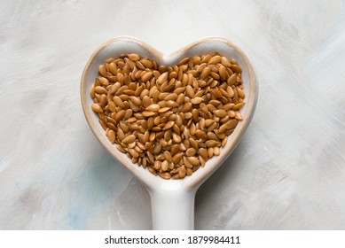 Gold Flaxseeds in a Heart Shaped Spoon