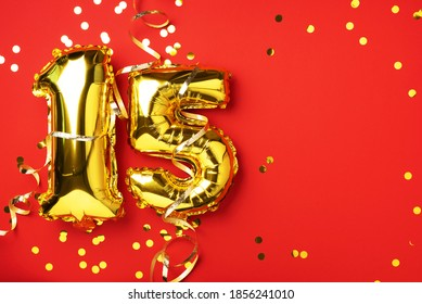 Gold foil balloon number, digit fifteen. Birthday greeting card, inscription 15. Anniversary celebration event. Banner. Stylish golden numeral, bright shiny glitter, red background. Numerical digit.