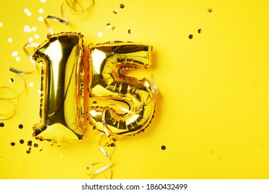 Gold foil balloon number, digit fifteen. Birthday greeting card, inscription 15. Anniversary celebration event. Banner. Stylish golden numeral, bright shiny glitter, yellow background. Numerical digit