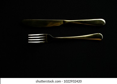 gold fork and knife, shot in a low key