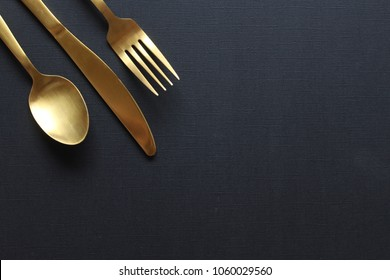 Gold fork, knife and spoon frame against  open black copy space.