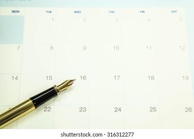 Gold fountain pen on calendar