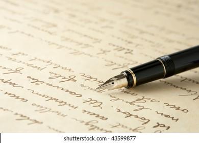 Gold Fountain Pen on Written Page. Crisp focus on nib of pen.