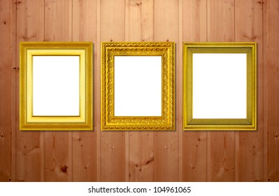 The gold frame on the wooden wall