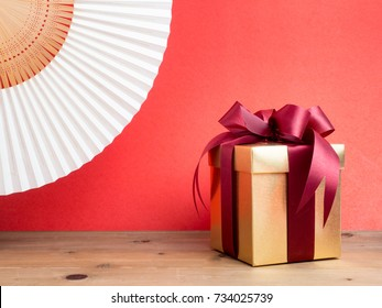 Gold gift box with red ribbon. Red background for create idea copy space.