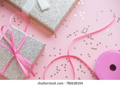 gold gift box and silver Christmas ball and ribbon on pink canvas background. Top view, flat lay. Close up. copy space for text, selective focus