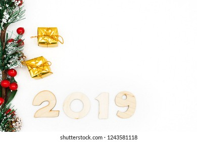 gold gift boxes, decorative spruce branch and symbol numbers 2019 New year on white background, simple flatley Christmas card. Selective focus.