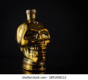 Gold glass skull on a dark background.
