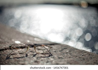 Gold glasses lying on the granite parapet of the river in St. Petersburg with a blurred background of water, highlights and bokeh. Backlighting.