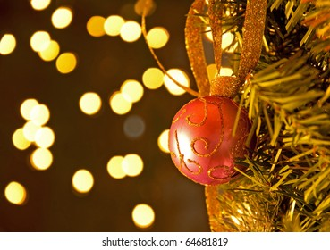 Gold glitter adorned Christmas ball hanging in a tree