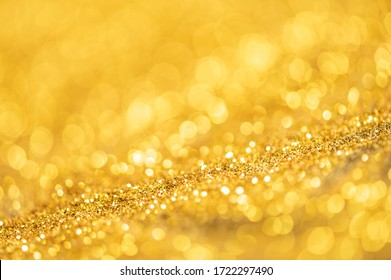 Gold glitter texture. Sparkling gold bright bokeh from blurred diamond dust. Abstract golden bokeh background. Selective focused