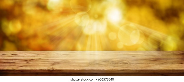 Gold glowing autumn background with empty wooden table for a concept
