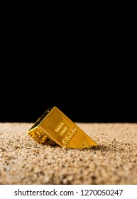 gold half sank into the sand in front of a black background concept of value collapsing of the gold