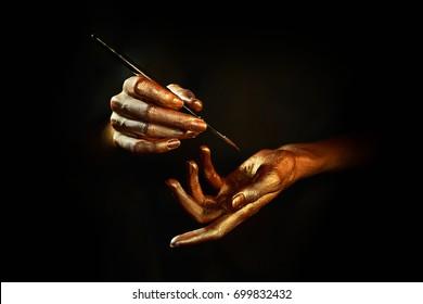 gold hands witn brush