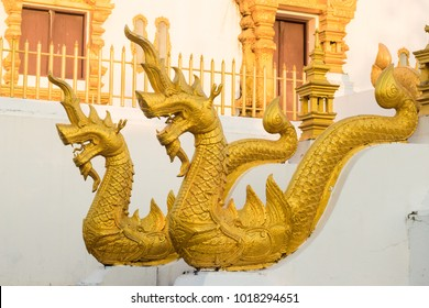 Gold head of king nagas statue from buddha's relics,Thailand.The corridor in front of the church,white temple