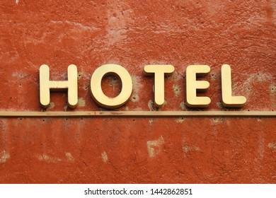 Gold hotel sign outside on building orange facade