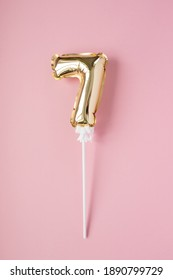 Gold inflatable number 7 on a stick on a pink background.
