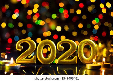 Gold inscription 2020, burning candles are on table. Festive decorative garland with red, green, yellow light bulbs, lanterns are shining on background. New year, christmas mood. Greeting card.