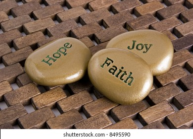 """Gold inspiration stones.  Etched with the words """"Hope"""", """"Faith:, and """"Joy""""."""