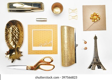 Gold items. Flat lay. Accessories on the table, woman desk top. View top table, background mock up. Envelope top