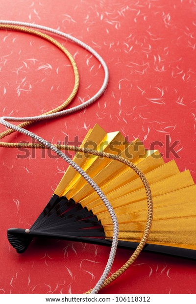 gold japanese fan on red background