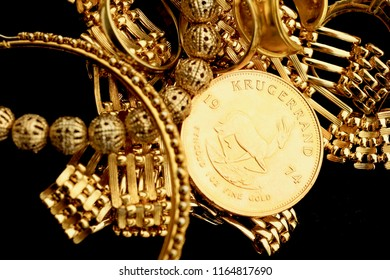 Gold jewelery and gold coin on black