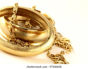 gold jewelry, bracelets and chains on a white background