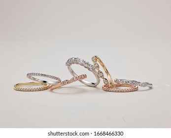 Gold jewelry bracelets with off white background focused on bracelets