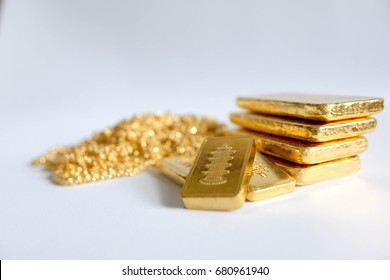 Gold jewelry and gold bullion on white background