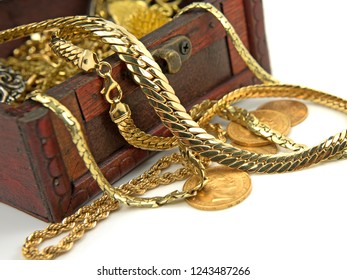 Gold jewelry and gold coins in a wooden box