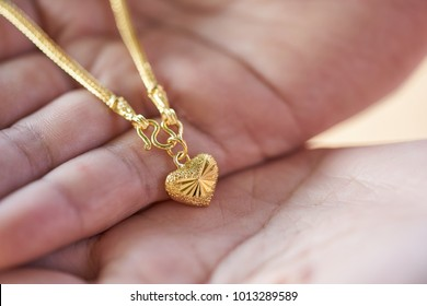 gold jewelry in lady hands.heart shape for girlfriend on Valentine's Day.