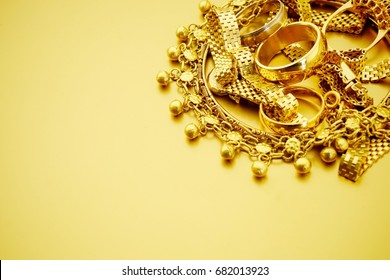 Gold jewelry on gold background with copy space
