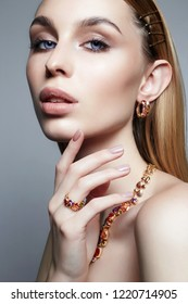 Gold jewelry on beautiful girl. young blonde woman with make-up and jewels accessories. Beauty Fashion Portrait