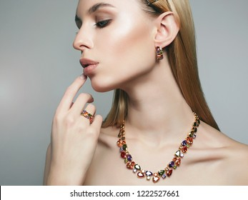 Gold jewelry on beautiful girl. young blonde woman with make-up and jewels accessories.