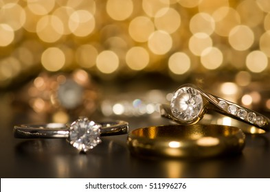 Gold jewelry on a black background. In the back of the golden light.