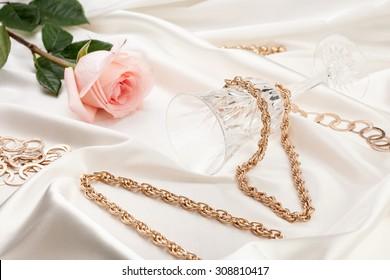 Gold jewelry, pink rose, wine glass on silk fabric