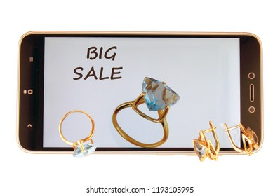 Gold jewelry with topazes on the screen of the smartphone. Big sale.On a white background.