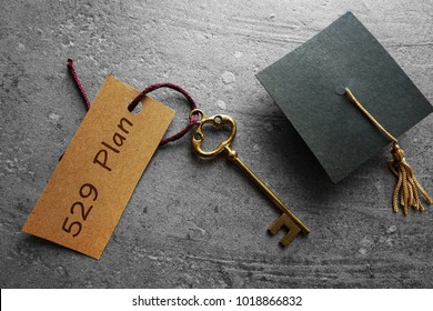 Gold key with 529 Plan tag and mini graduation cap -- college savings concept